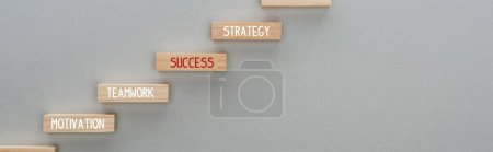 Photo for Panoramic shot of wooden blocks with motivation, teamwork, success, strategy words on grey background, business concept - Royalty Free Image