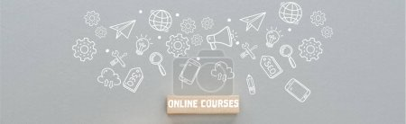Photo pour Panoramic shot of wooden block with online courses inscription and multimedia icons illustration on grey background, business concept - image libre de droit
