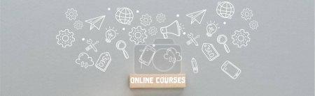 Foto de Panoramic shot of wooden block with online courses inscription and multimedia icons illustration on grey background, business concept - Imagen libre de derechos