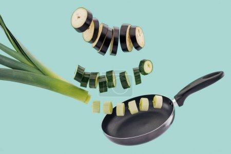 Photo pour Légumes biologiques tranchés frais au-dessus de la casserole d'isolement sur le turquoise - image libre de droit