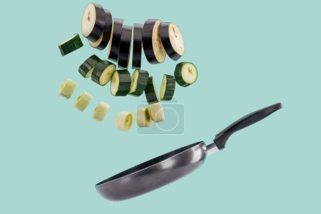Photo for Sliced green organic tasty vegetables above frying pan isolated on turquoise - Royalty Free Image