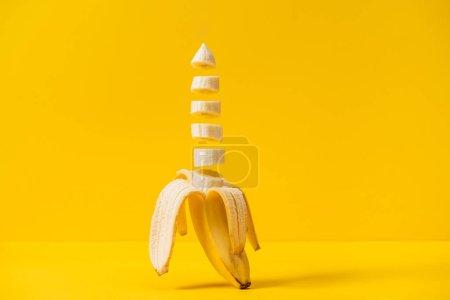 Foto de Sliced tropic sweet delicious banana isolated on yellow - Imagen libre de derechos