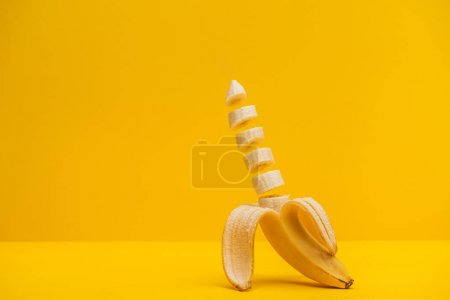 Photo for Half sliced fresh sweet tasty banana isolated on yellow - Royalty Free Image