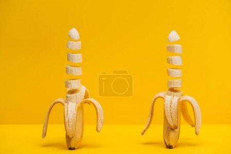 Photo pour Deux délicieuses bananes fraîchement tranchées isolées sur du jaune - image libre de droit
