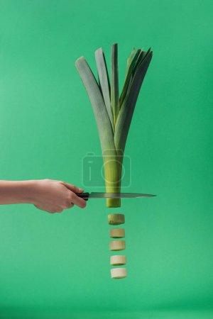 Photo pour Vue partielle de femme retenant le couteau et coupant le poireau frais vert sur le vert - image libre de droit
