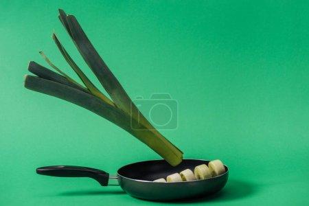 Photo pour Poireau délicieux frais vert dans la poêle sur le fond vert - image libre de droit