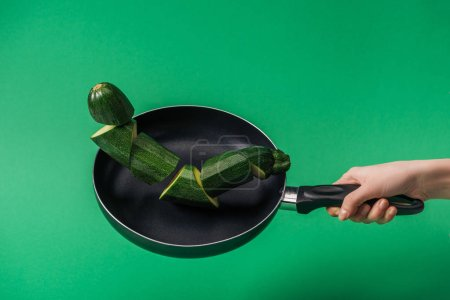Photo for Partial view of woman holding frying pan with fresh green sliced zucchini on green background - Royalty Free Image