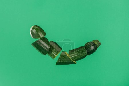 Photo for Freshly sliced organic green zucchini isolated on green - Royalty Free Image