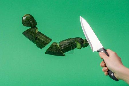Photo pour Vue cultivée de couteau de fixation de femme avec les courgettes vertes fraîches tranchées d'isolement sur le vert - image libre de droit