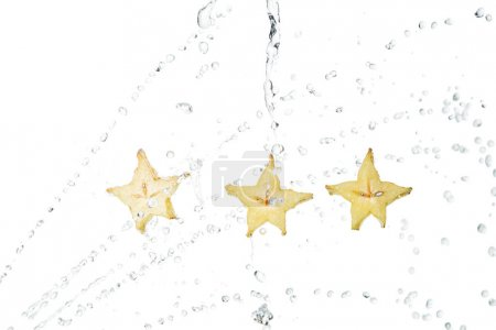 wet exotic star fruit slices and water drops isolated on white