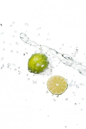 Photo for Green fresh whole lime and half with clear water splash and drops isolated on white - Royalty Free Image