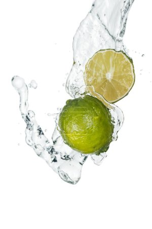 Photo for Green fresh whole lime and half with clear water stream and drops isolated on white - Royalty Free Image