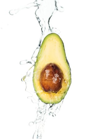 Photo for Ripe nutritious avocado half with seed and water splash isolated on white - Royalty Free Image