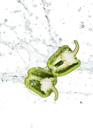 Photo for Fresh green bell pepper halves and water splash with drops isolated on white - Royalty Free Image