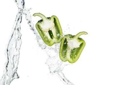 Photo for Ripe green bell pepper halves and clear water streams with drops isolated on white - Royalty Free Image
