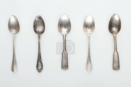 Photo for Top view of shiny aged silver empty spoons in row on white background - Royalty Free Image