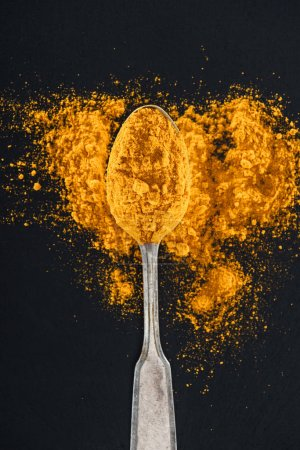 Photo for Top view of curry powder in silver spoon on black background - Royalty Free Image