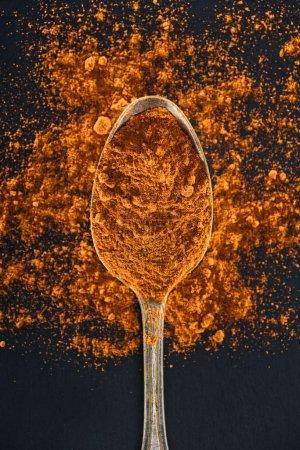 Photo pour Vue supérieure du curcuma dans la cuillère argentée sur le fond noir - image libre de droit