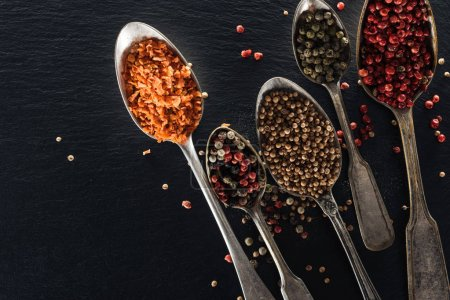 Photo for Top view of pepper, candied fruit and mustard in silver spoons on black textured background - Royalty Free Image