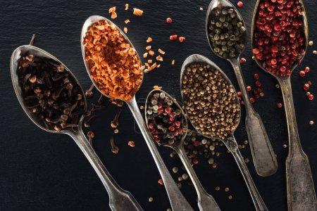 Photo pour Vue supérieure du poivre, du fruit confit, de la coriandre et des graines d'oeillet dans des cuillères argentées sur le fond texturé noir - image libre de droit