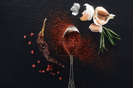 Photo for Top view of red pepper powder in silver spoon on black background with dried chili peppe, herbs and garlic - Royalty Free Image