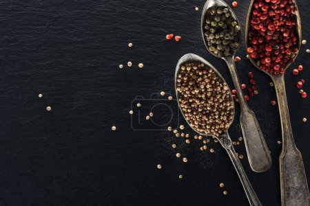 Photo for Top view of pepper and coriander seeds in silver spoons on black textured background - Royalty Free Image