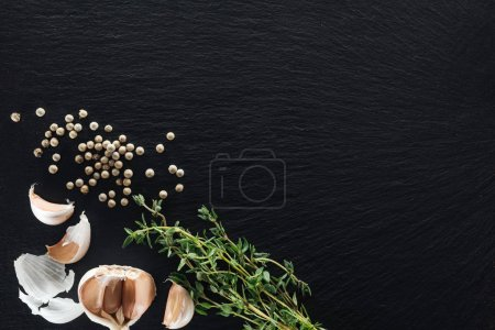 Photo for Top view of white pepper on black background near garlic cloves and thyme - Royalty Free Image
