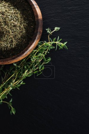 Photo for Top view of dried thyme in wooden bowl near green herb on black background - Royalty Free Image