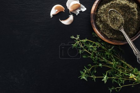 Photo for Top view of dried thyme in wooden bowl with silver spoon near green herb and garlic cloves on black background - Royalty Free Image