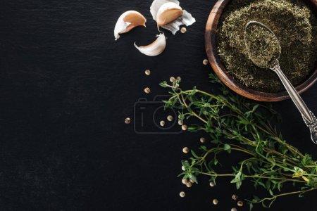 Photo pour Vue supérieure du thym séché dans le bol en bois avec la cuillère argentée près de l'herbe verte, du poivre blanc et des gousses d'ail sur le fond noir - image libre de droit