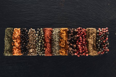 Photo for Top view of traditional bright indian spices on textured black background - Royalty Free Image
