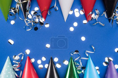 Foto de Top view of party hats and silver confetti on blue background - Imagen libre de derechos