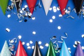 "Постер, картина, фотообои ""Top view of party hats and silver confetti on blue background"""