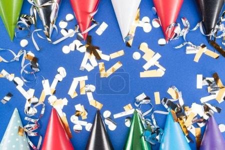 Foto de Colorful party hats and silver confetti on blue background - Imagen libre de derechos