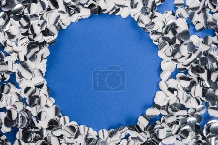 Foto de Top view of silver circle made of confetti on blue background - Imagen libre de derechos