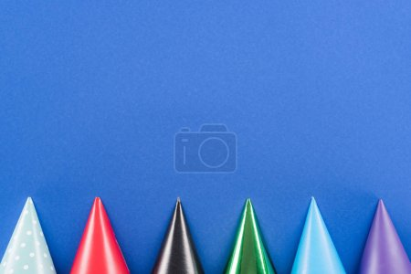 Foto de Top view of multicolored party hats on blue background - Imagen libre de derechos