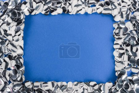 Foto de Top view of silver confetti frame on blue background - Imagen libre de derechos