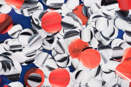 Photo for Close up view of silver and red confetti on blue background - Royalty Free Image