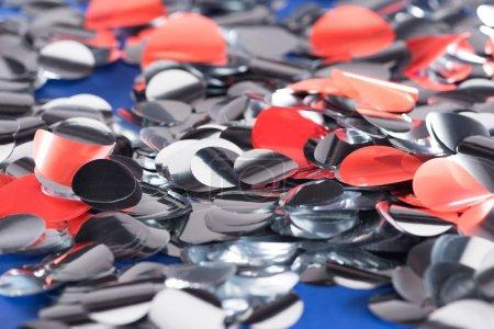 Foto de Selective focus of silver and red confetti on blue background - Imagen libre de derechos