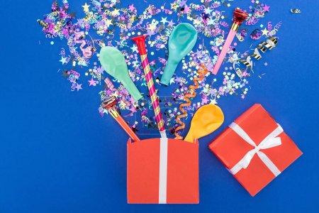 Foto de Caja de regalo roja y decoración de fiesta sobre fondo azul - Imagen libre de derechos