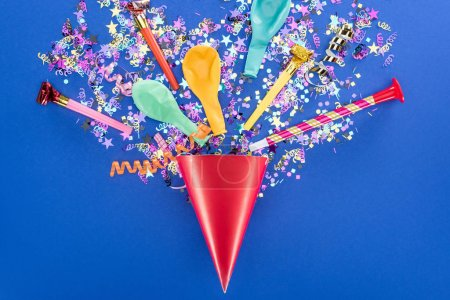 Photo for Top view of festive red party hat on blue background - Royalty Free Image