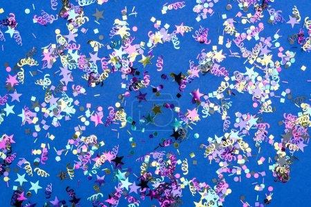 Foto de Top view of colorful sparkling confetti on blue background - Imagen libre de derechos
