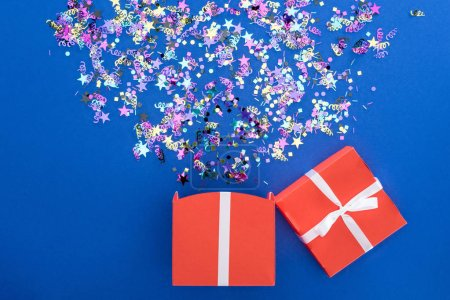 Photo pour Red gift box and multicolored shiny confetti on blue background - image libre de droit