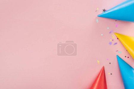Foto de Vista superior de sombreros de fiesta y confeti sobre fondo rosa - Imagen libre de derechos