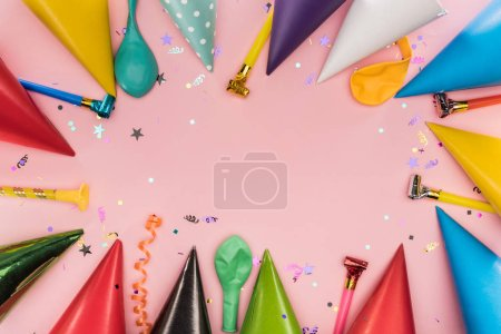 Foto de Top view of party horns, caps and confetti on pink background - Imagen libre de derechos