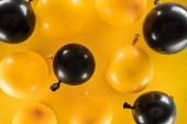 "Постер, картина, фотообои ""Top view of yellow and black balloons on bright background"""