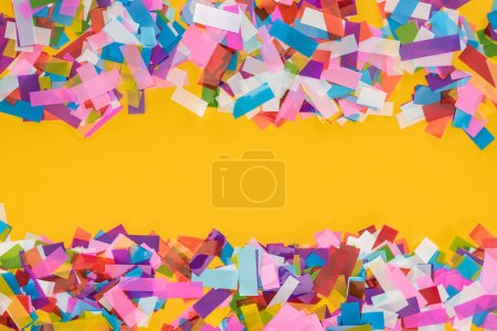 Top view of multicolored confetti frame on yellow background