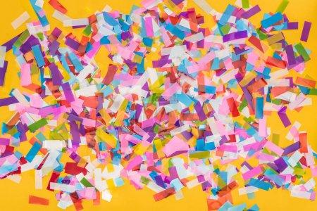 Photo pour Top view of colorful confetti on yellow party background - image libre de droit