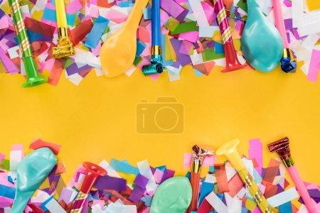 Foto de Multicolored party decoration frame on yellow background - Imagen libre de derechos