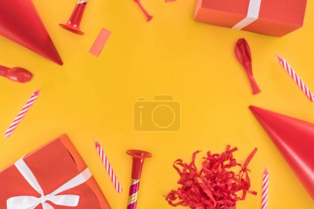 Photo for Red birthday party objects on yellow background - Royalty Free Image